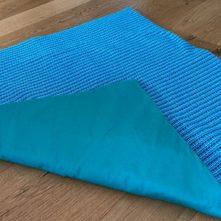 Die Decke ist wattiert. Die Unterseite besteht aus einem robusten Baumwollstoff.