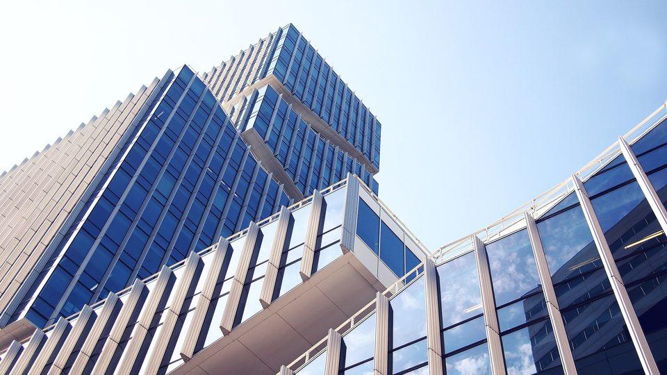 repräsentatives Bürogebäude mit moderner sowie futuristischer Glasfassade und blauem Himmel
