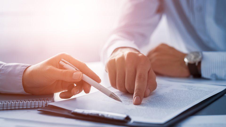 Sorgfältige und professionelle Immobilienverwaltung wird durch menschliche Hände sowie Unterlagen dargestellt