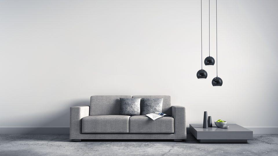 Wohnliches Raumgefühl einer Privatimmobilie durch ein graues Sofa, moderne Lampen vor einer weißen Wand